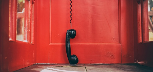 phone hanging from the line in a phone booth | put complex union pay policies behind you