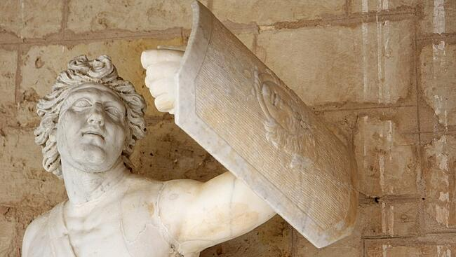 Greek statue holding a shield in self defense | protect your company from employee lawsuits