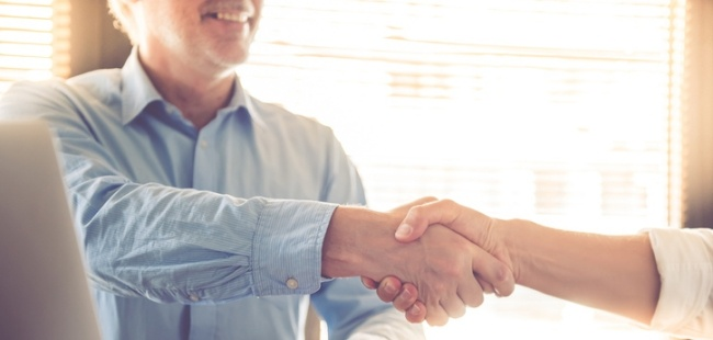 non-profit CFO shaking hands with an HCM sales rep