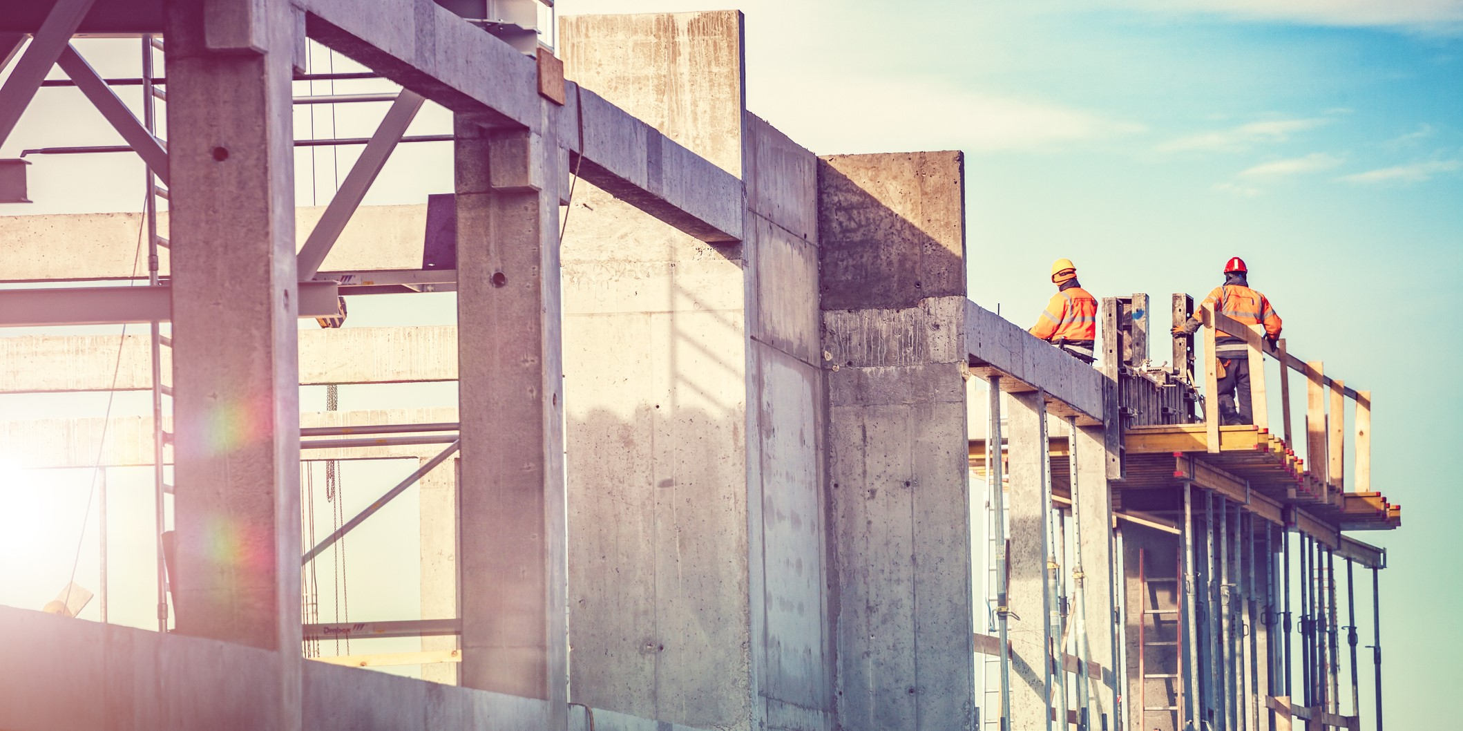 construction site with workers in the background | solutions for challenging construction payroll complexities