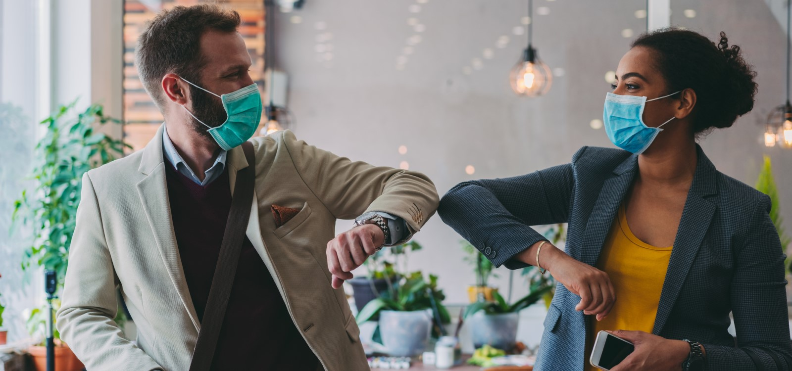 Business people greeting during COVID-19 pandemic, elbow bump | coronavirus for businesses in multiple states