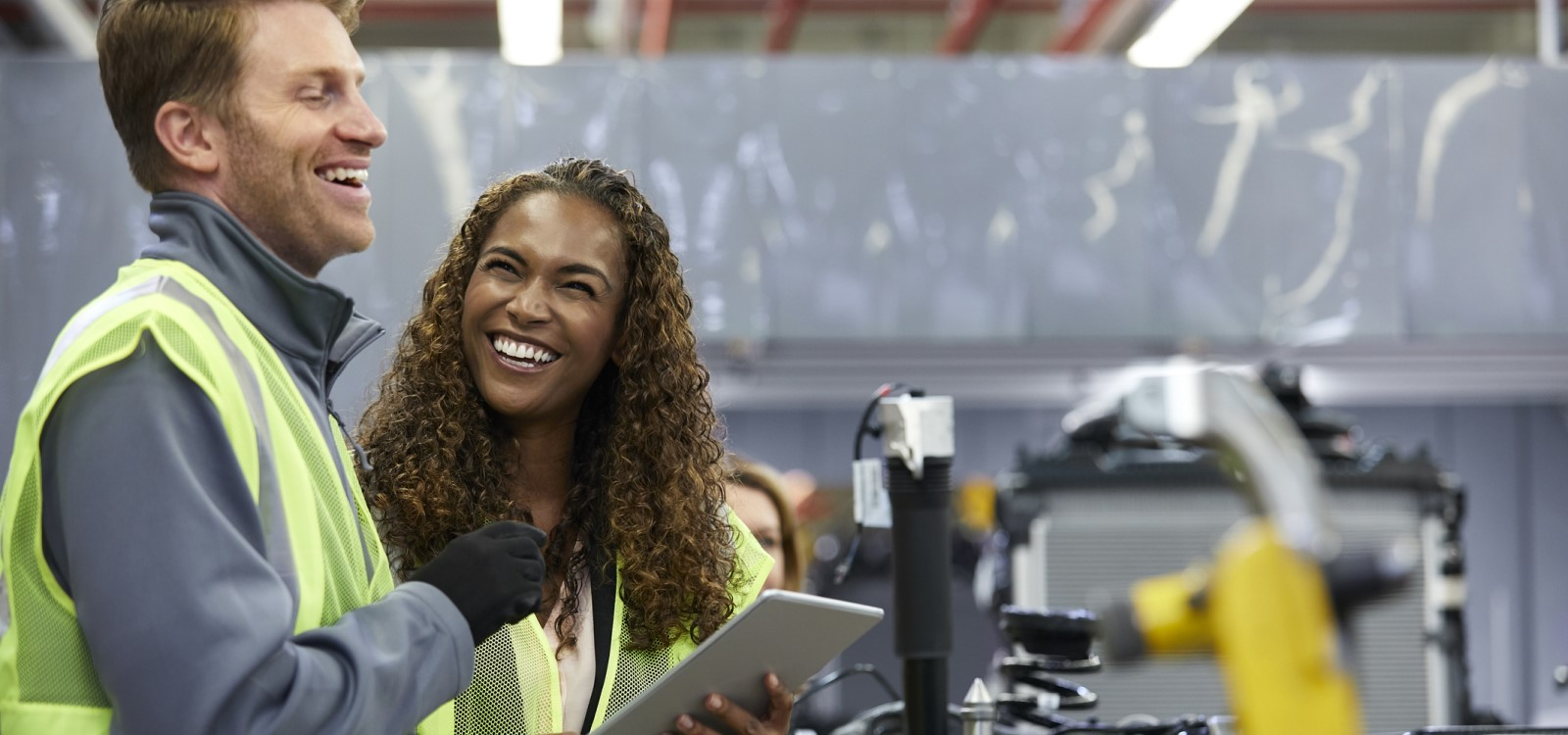 smiling workers in a manufacturing plant | top issues your new payroll software needs to solve