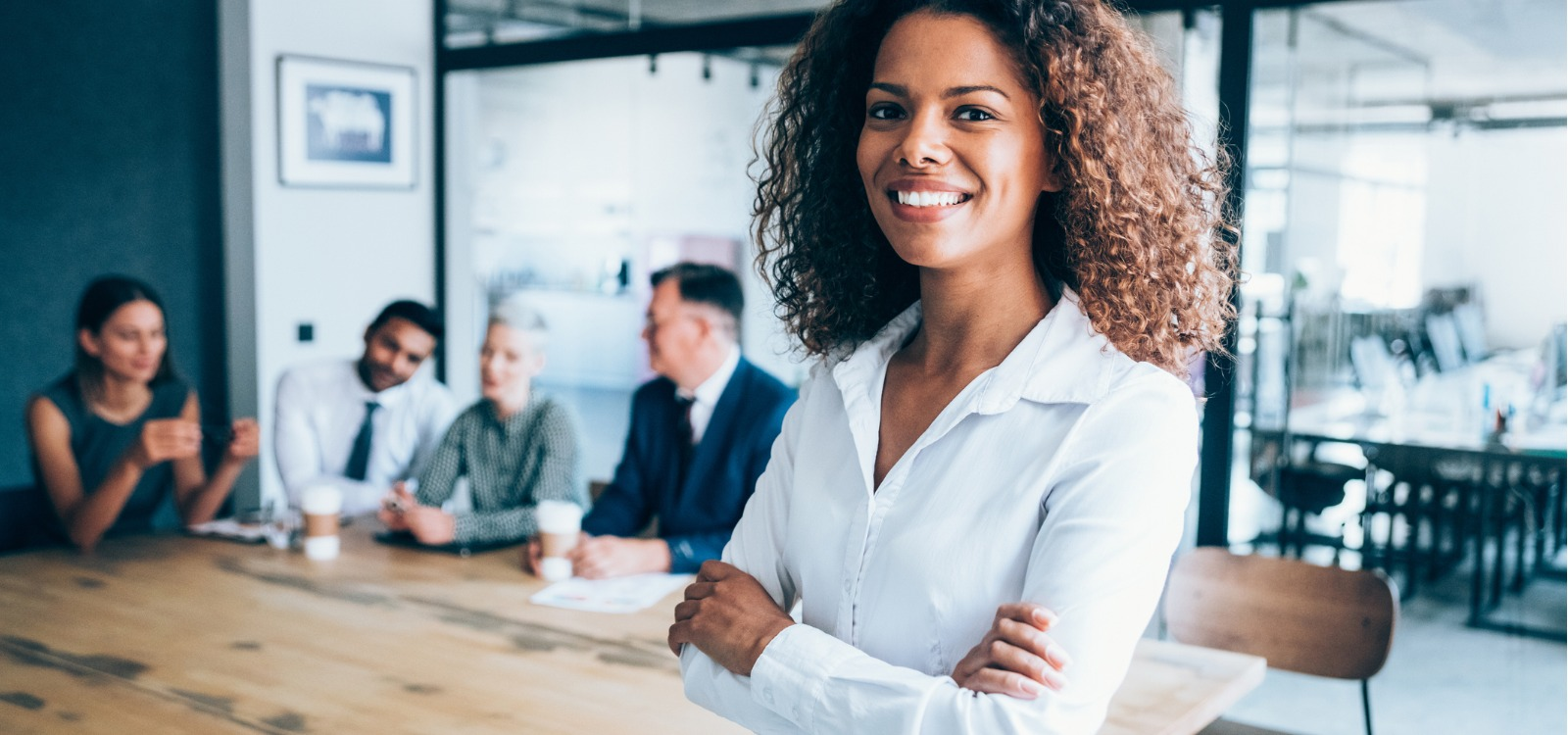 businesswoman standing with arms crossed in front of her team | grow your business during challenging times
