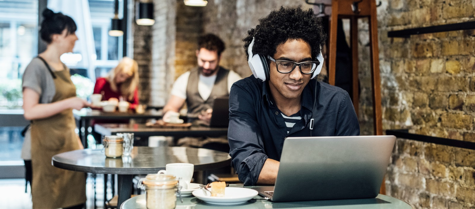 Gen Z man working remotely in a coffee shop as part of the gig economy