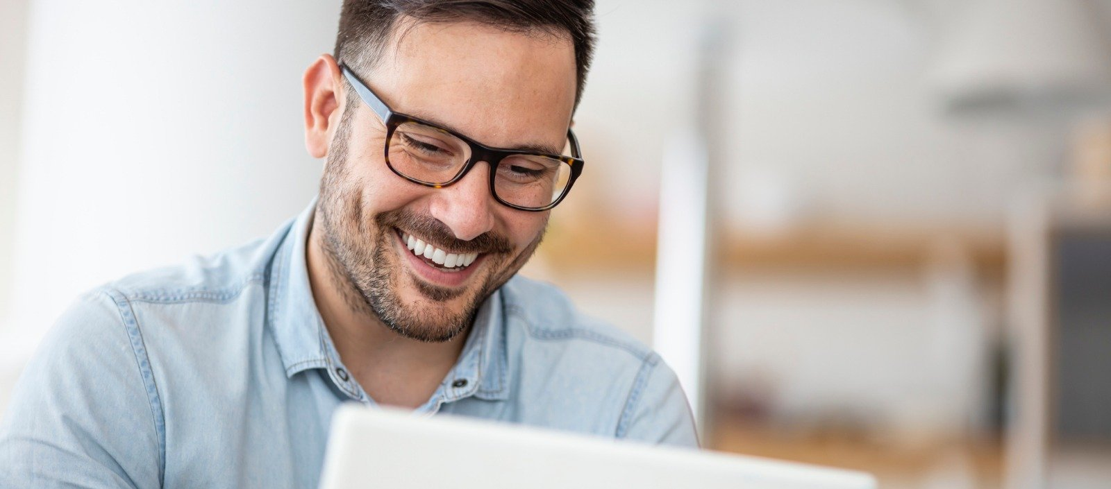 HCM sales representative at his laptop, smiling because he wrote a follow-up sales email that got results
